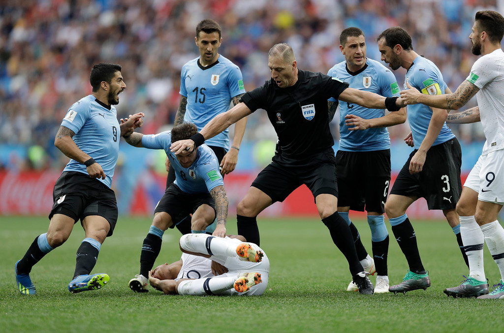 . Uruguay players protest to referee Nestor Pitana of Argentina that France\'s Kylian Mbappe, on the ground, is overreacting after taking a dive during the quarterfinal match between Uruguay and France at the 2018 soccer World Cup in the Nizhny Novgorod Stadium, in Nizhny Novgorod, Russia, Friday, July 6, 2018. (AP Photo/Natacha Pisarenko)