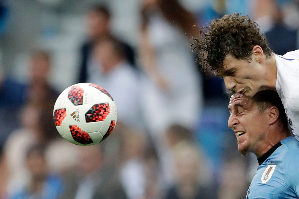. France\'s Benjamin Pavard, top, and Uruguay\'s Cristian Rodriguez challenge for the ball during the quarterfinal match between Uruguay and France at the 2018 soccer World Cup in the Nizhny Novgorod Stadium, in Nizhny Novgorod, Russia, Friday, July 6, 2018. (AP Photo/Petr David Josek)