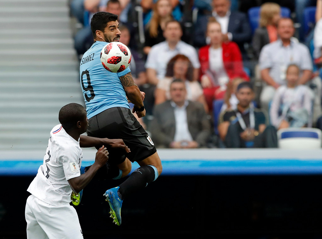 . Uruguay\'s Luis Suarez, top, jumps for the ball with France\'s Ngolo Kante during the quarterfinal match between Uruguay and France at the 2018 soccer World Cup in the Nizhny Novgorod Stadium, in Nizhny Novgorod, Russia, Friday, July 6, 2018. (AP Photo/Ricardo Mazalan)