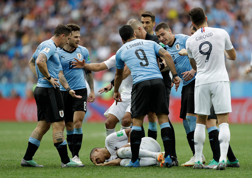 . Uruguay players argue that France\'s Kylian Mbappe, on the ground, is overreacting after taking a dive during the quarterfinal match between Uruguay and France at the 2018 soccer World Cup in the Nizhny Novgorod Stadium, in Nizhny Novgorod, Russia, Friday, July 6, 2018. (AP Photo/Natacha Pisarenko)