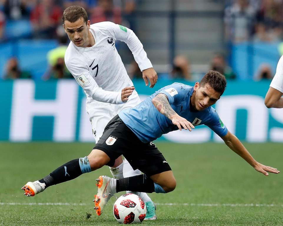 . France\'s Antoine Griezmann, left, and Uruguay\'s Lucas Torreira, right, challenge for the ball during the quarterfinal match between Uruguay and France at the 2018 soccer World Cup in the Nizhny Novgorod Stadium, in Nizhny Novgorod, Russia, Friday, July 6, 2018. (AP Photo/David Vincent)