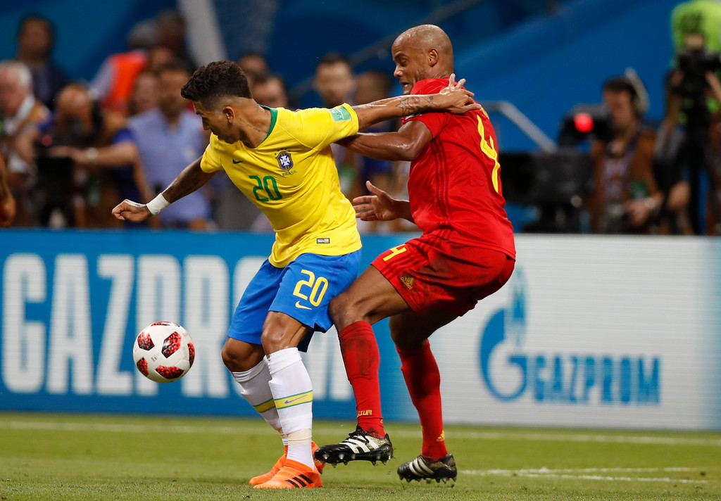 . Brazil\'s Roberto Firmino, left, and Belgium\'s Vincent Kompany challenge for the ball during the quarterfinal match between Brazil and Belgium at the 2018 soccer World Cup in the Kazan Arena, in Kazan, Russia, Friday, July 6, 2018. (AP Photo/Francisco Seco)