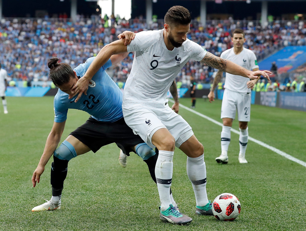 . Uruguay\'s Martin Caceres, left, and France\'s Olivier Giroud, right, challenge for the ball during the quarterfinal match between Uruguay and France at the 2018 soccer World Cup in the Nizhny Novgorod Stadium, in Nizhny Novgorod, Russia, Friday, July 6, 2018. (AP Photo/David Vincent)