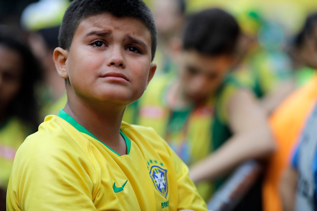 . A young Brazil soccer fan cries at the end of a live broadcast of the World Cup quarterfinal match between Brazil and Belgium in Rio de Janeiro, Brazil, Friday, July 6, 2018. Belgium knocked Brazil out of the World Cup and advanced to the semi-finals.  (AP Photo/Leo Correa)