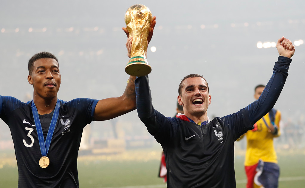 . France\'s Antoine Griezmann, right with teammate France\'s Presnel Kimpembe hold the World Cup trophy as they celebrate after final match between France and Croatia at the 2018 soccer World Cup in the Luzhniki Stadium in Moscow, Russia, Sunday, July 15, 2018. France defeated Croatia 4-2. (AP Photo/Francisco Seco)