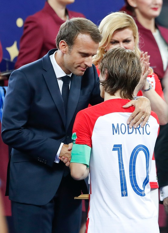 . French President Emmanuel Macron is flanked by Croatian President Kolinda Grabar-Kitarovic as he shakes hands with Croatia\'s Luka Modric at the end of the final match between France and Croatia at the 2018 soccer World Cup in the Luzhniki Stadium in Moscow, Russia, Sunday, July 15, 2018. France won 4-2. (AP Photo/Petr David Josek)