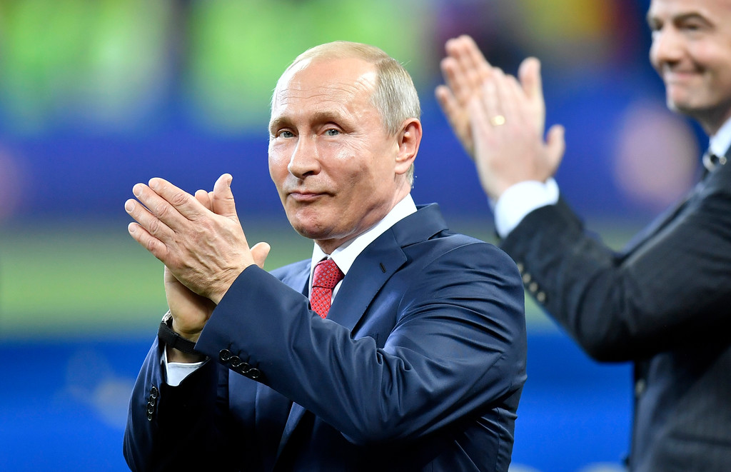 . Russian President Vladimir Putin applauds in front of FIFA President Gianni Infantino after the final match between France and Croatia at the 2018 soccer World Cup in the Luzhniki Stadium in Moscow, Russia, Sunday, July 15, 2018. (AP Photo/Martin Meissner)