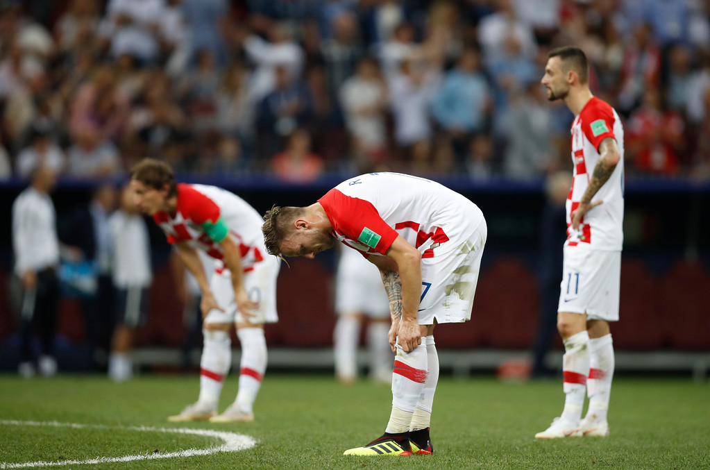 . Croatia\'s Ivan Rakitic, center pulls up his socks as he waits for the restart after France scored their 4th goal of the game during the final match between France and Croatia at the 2018 soccer World Cup in the Luzhniki Stadium in Moscow, Russia, Sunday, July 15, 2018. (AP Photo/Francisco Seco)