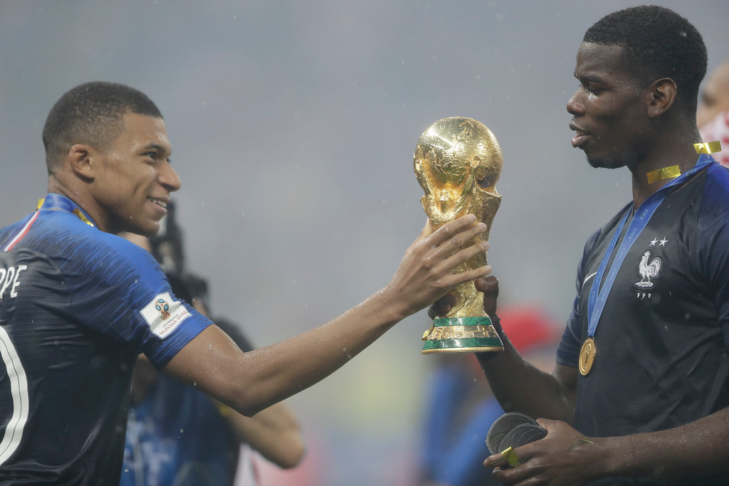 . France\'s Kylian Mbappe hands the trophy to Paul Pogba after the final match between France and Croatia at the 2018 soccer World Cup in the Luzhniki Stadium in Moscow, Russia, Sunday, July 15, 2018. (AP Photo/Natacha Pisarenko)