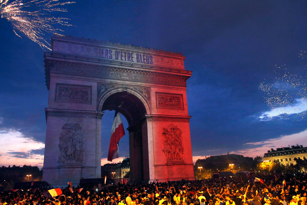 . The Arc de Triomphe is illuminated with the colors of the French national flag and by fireworks set off by French soccer fans celebrating France\'s World Cup victory over Croatia, in Paris, France, Sunday, July 15, 2018. France won the final 4-2. The inscription in French reads : Proud to be blue (French) . (AP Photo/Thibault Camus)