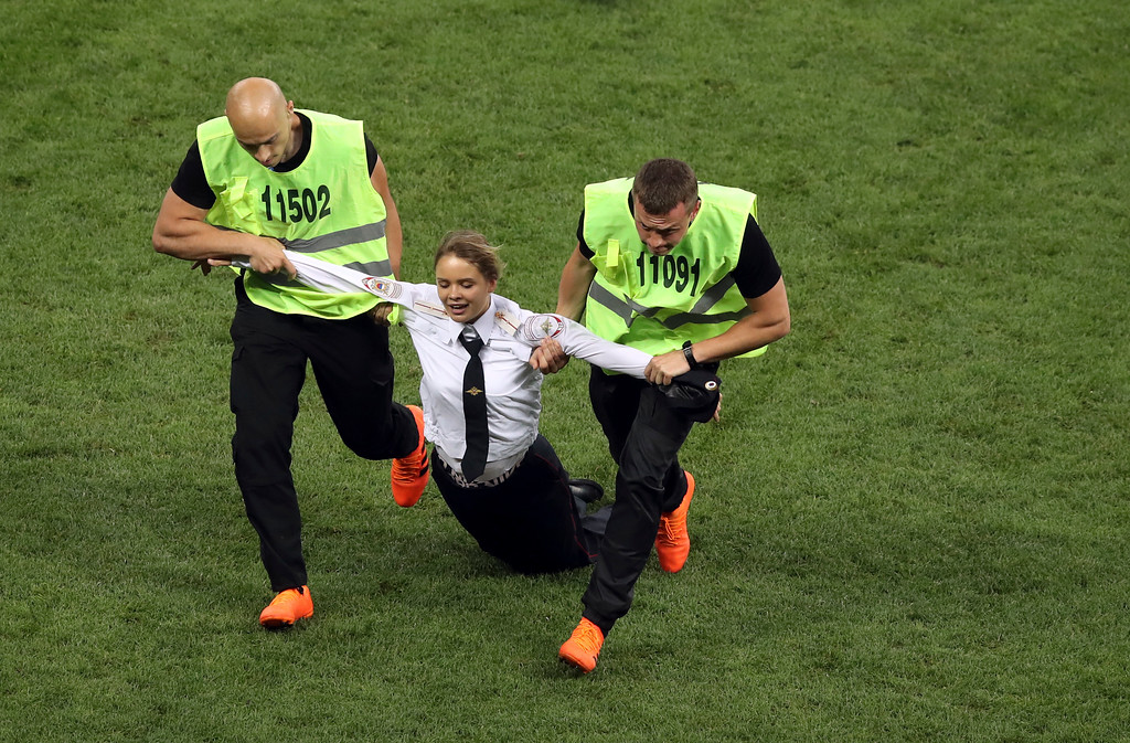 . Stewards drag a woman who invaded the pitch during the final match between France and Croatia at the 2018 soccer World Cup in the Luzhniki Stadium in Moscow, Russia, Sunday, July 15, 2018. (AP Photo/Thanassis Stavrakis)