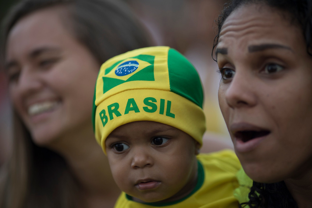 . A woman carries a baby wearing Brazil\'s colors as she watch a live telecast of their team\'s World Cup match against Serbia, at the Manguinhos slum in Rio de Janeiro, Brazil, Wednesday, June 27, 2018. (AP Photo/Leo Correa)