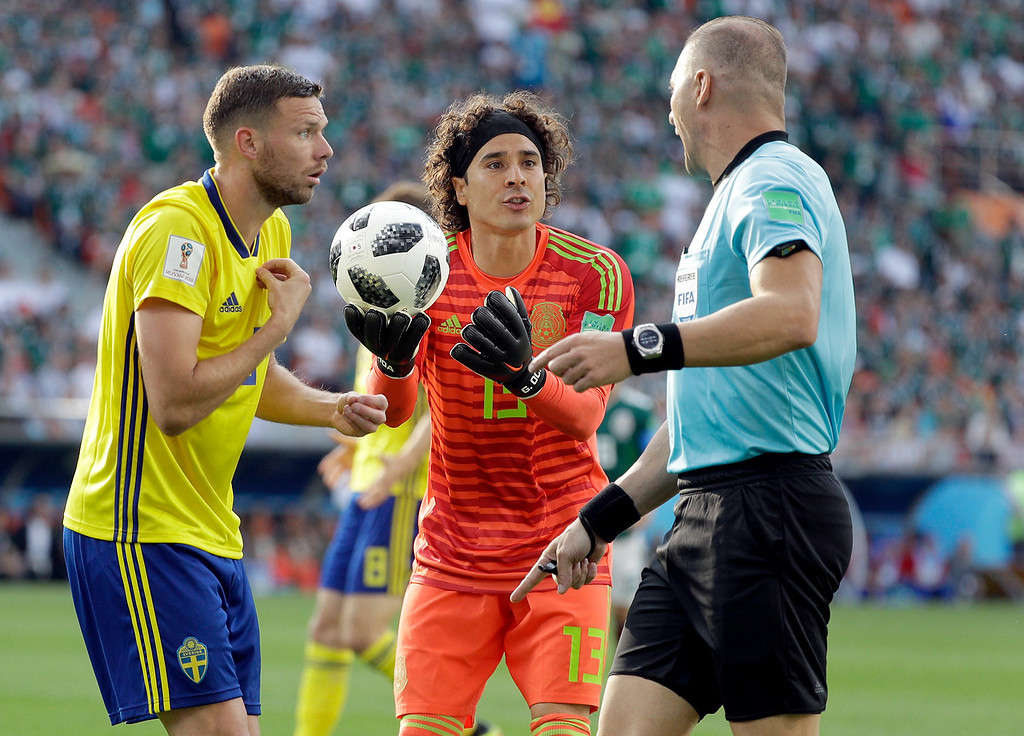 . Sweden\'s Marcus Berg, left, and Mexico goalkeeper Guillermo Ochoa, center, gesture as referee Nestor Pitana, right, points down during the group F match between Mexico and Sweden, at the 2018 soccer World Cup in the Yekaterinburg Arena in Yekaterinburg , Russia, Wednesday, June 27, 2018. (AP Photo/Gregorio Borgia)