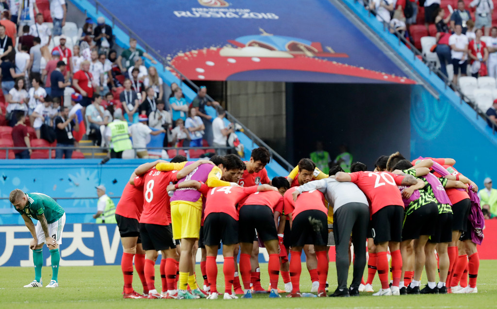 . Germany\'s Toni Kroos, left, as South Korea\'s players huddle after the group F match between South Korea and Germany, at the 2018 soccer World Cup in the Kazan Arena in Kazan, Russia, Wednesday, June 27, 2018. (AP Photo/Lee Jin-man)