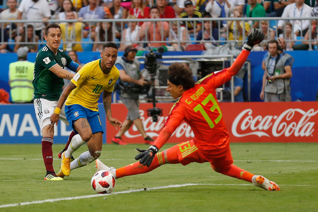 . Brazil\'s Neymar, background center, passes the ball to team mate Roberto Firmino scoring his side\'s second goal during the round of 16 match between Brazil and Mexico at the 2018 soccer World Cup in the Samara Arena, in Samara, Russia, Monday, July 2, 2018. (AP Photo/Frank Augstein)