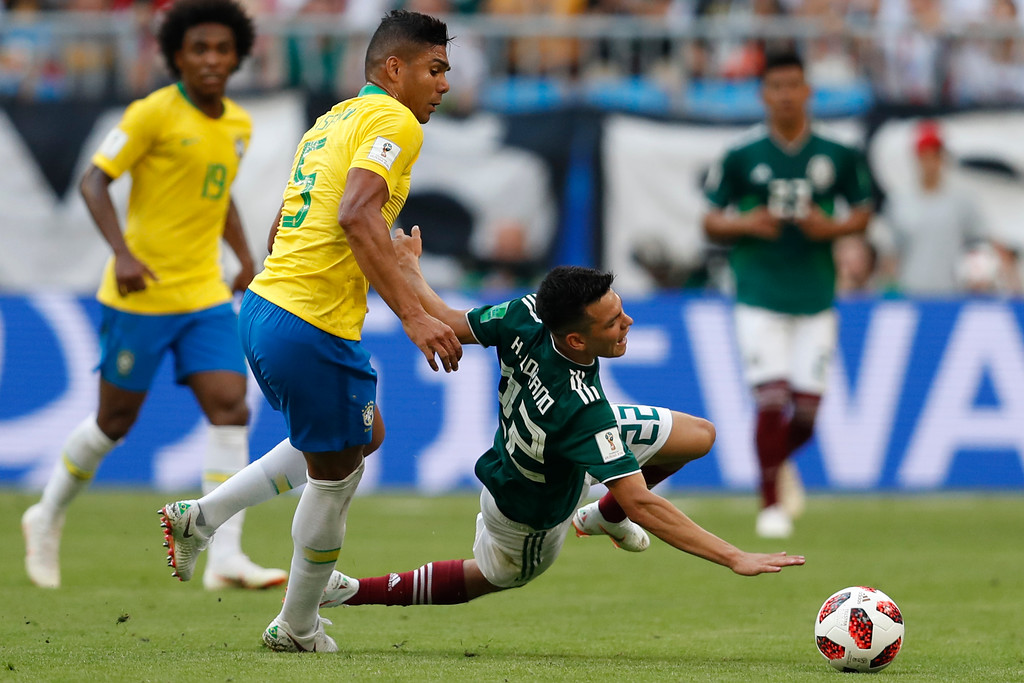 . Mexico\'s Hirving Lozano falls fouled by Brazil\'s Casemiro during the round of 16 match between Brazil and Mexico at the 2018 soccer World Cup in the Samara Arena, in Samara, Russia, Monday, July 2, 2018. (AP Photo/Eduardo Verdugo)
