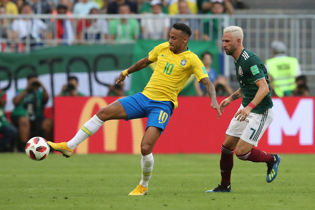 . Brazil\'s Neymar, left, lunges for the ball against Mexico\'s Miguel Layun during the round of 16 match between Brazil and Mexico at the 2018 soccer World Cup in the Samara Arena, in Samara, Russia, Monday, July 2, 2018. (AP Photo/Thanassis Stavrakis)