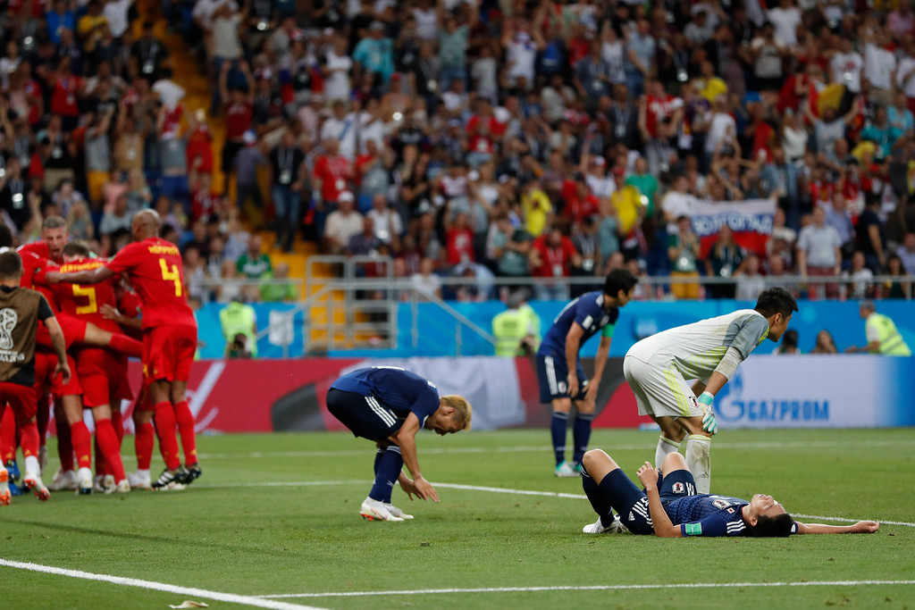 . Japanese players stand on the pitch as Belgium players, left, celebrate their side\'s third goal scored by Nacer Chadli during the round of 16 match between Belgium and Japan at the 2018 soccer World Cup in the Rostov Arena, in Rostov-on-Don, Russia, Monday, July 2, 2018. Belgium won 3-2. (AP Photo/Natacha Pisarenko)