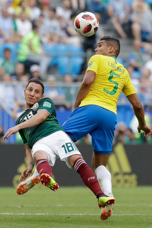 . Brazil\'s Casemiro jumps for the ball with Mexico\'s Andres Guardado, left, during the round of 16 match between Brazil and Mexico at the 2018 soccer World Cup in the Samara Arena, in Samara, Russia, Monday, July 2, 2018. (AP Photo/Andre Penner)