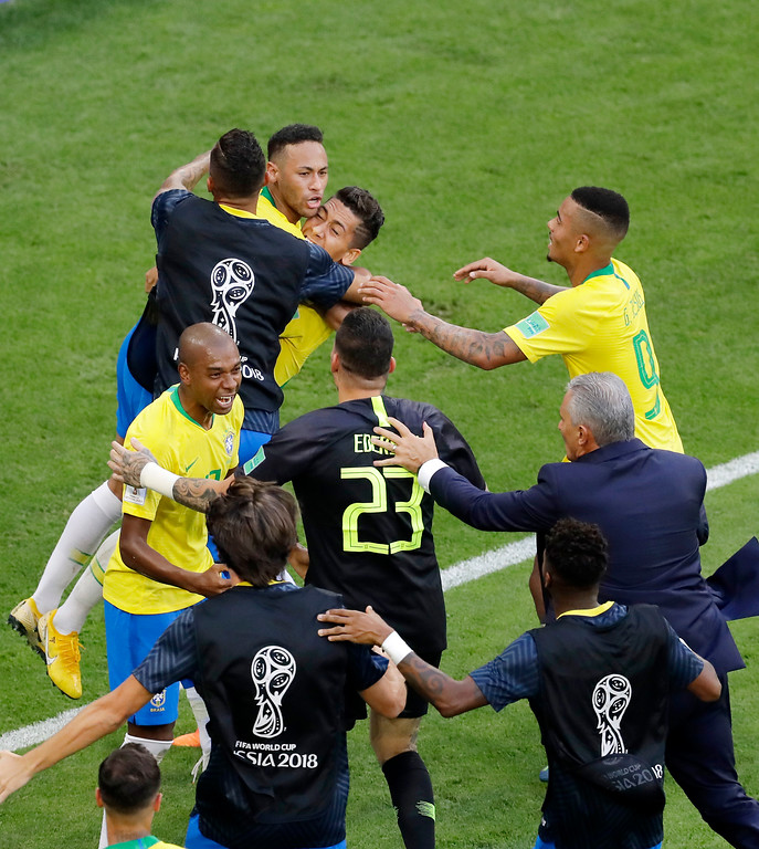 . Brazil\'s Roberto Firmino celebrates with his teammates ad his head coach Tite, second from right, after scoring his side\'s second goalduring the round of 16 match between Brazil and Mexico at the 2018 soccer World Cup in the Samara Arena, in Samara, Russia, Monday, July 2, 2018. (AP Photo/Sergei Grits)