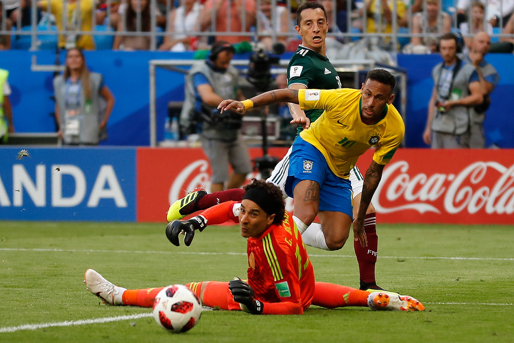. Brazil\'s Neymar, background center, passes the ball to team mate Roberto Firmino behind Mexico goalkeeper Guillermo Ochoa during the round of 16 match between Brazil and Mexico at the 2018 soccer World Cup in the Samara Arena, in Samara, Russia, Monday, July 2, 2018. (AP Photo/Frank Augstein)