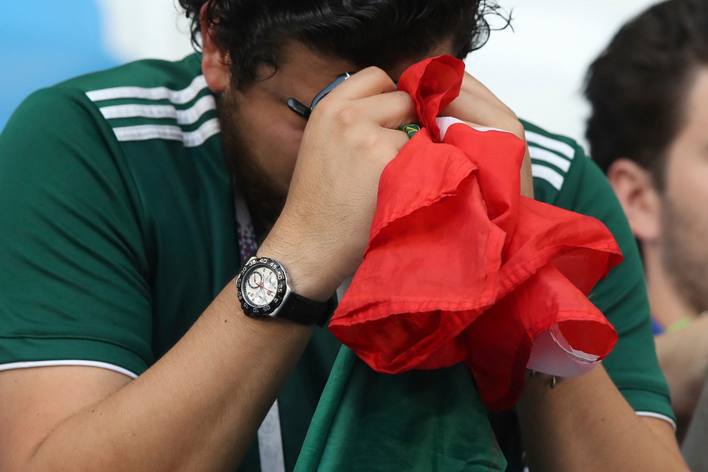 . A Mexican fan hides his face behind a Mexico flag at the end of the round of 16 match between Brazil and Mexico at the 2018 soccer World Cup in the Samara Arena, in Samara, Russia, Monday, July 2, 2018. Brazil defeated Mexico 2-0. (AP Photo/Thanassis Stavrakis)