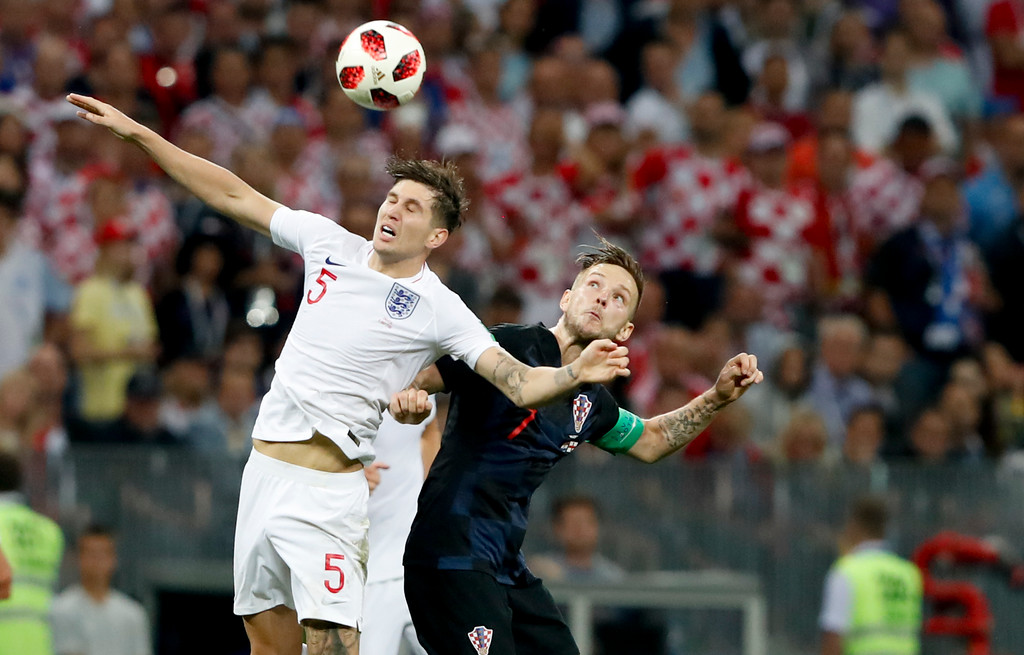 . England\'s John Stones, left, challenges for the ball with Croatia\'s Ivan Rakitic during the semifinal match between Croatia and England at the 2018 soccer World Cup in the Luzhniki Stadium in Moscow, Russia, Wednesday, July 11, 2018. (AP Photo/Rebecca Blackwell)