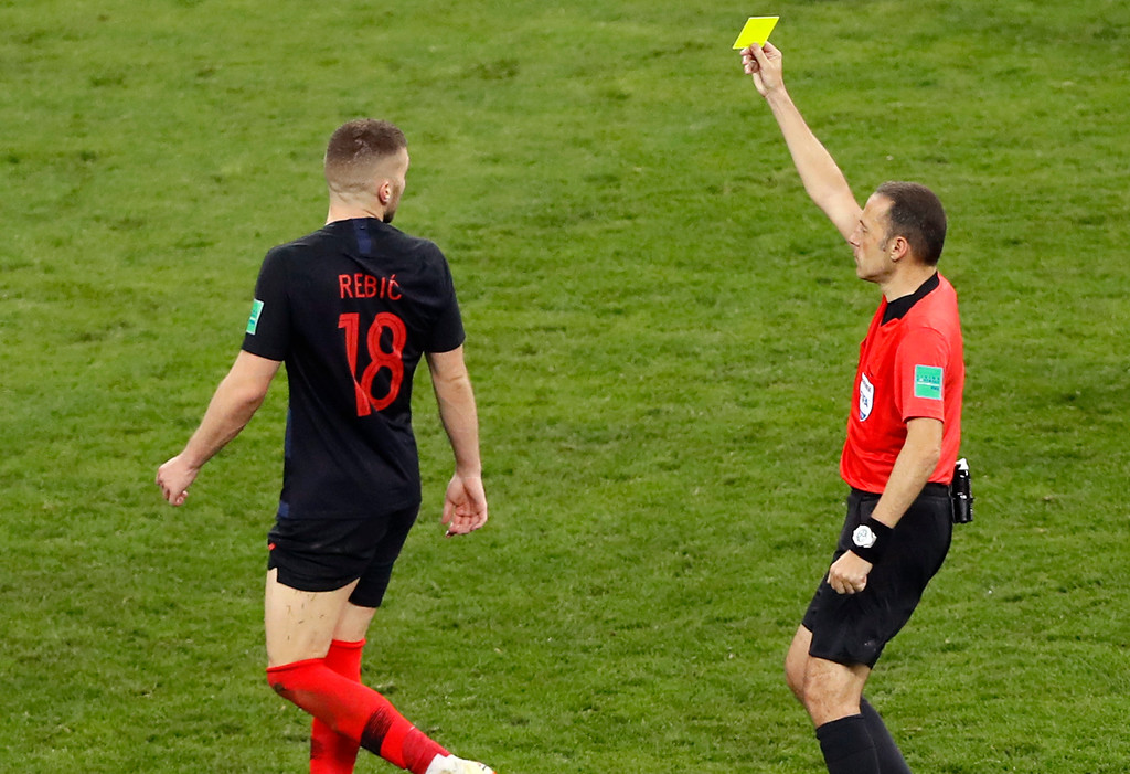 . Referee Cuneyt Cakir, right, shows a yellow card to Croatia\'s Ante Rebic during the semifinal match between Croatia and England at the 2018 soccer World Cup in the Luzhniki Stadium in Moscow, Russia, Wednesday, July 11, 2018. (AP Photo/Darko Bandic)
