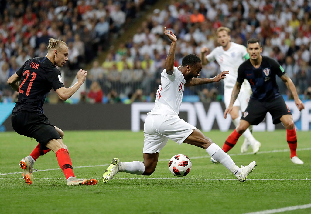 . England\'s Raheem Sterling, center, falls over the shoe of Croatia\'s Domagoj Vida during the semifinal match between Croatia and England at the 2018 soccer World Cup in the Luzhniki Stadium in Moscow, Russia, Wednesday, July 11, 2018. (AP Photo/Matthias Schrader)