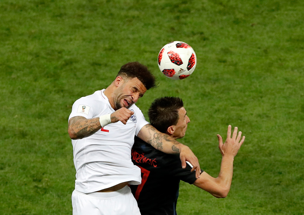 . England\'s Kyle Walker, left, jumps for the ball with Croatia\'s Mario Mandzukic during the semifinal match between Croatia and England at the 2018 soccer World Cup in the Luzhniki Stadium in Moscow, Russia, Wednesday, July 11, 2018. (AP Photo/Darko Bandic)