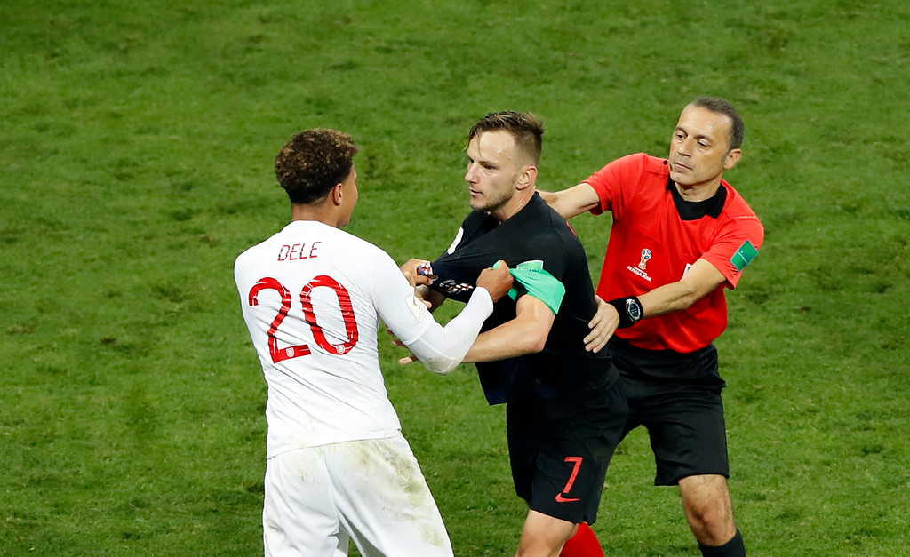 . Croatia\'s Ivan Rakitic, center, and England\'s Dele Alli, left, are separated by referee Cuneyt Cakir from Turkey during the semifinal match between Croatia and England at the 2018 soccer World Cup in the Luzhniki Stadium in Moscow, Russia, Wednesday, July 11, 2018. (AP Photo/Darko Bandic)