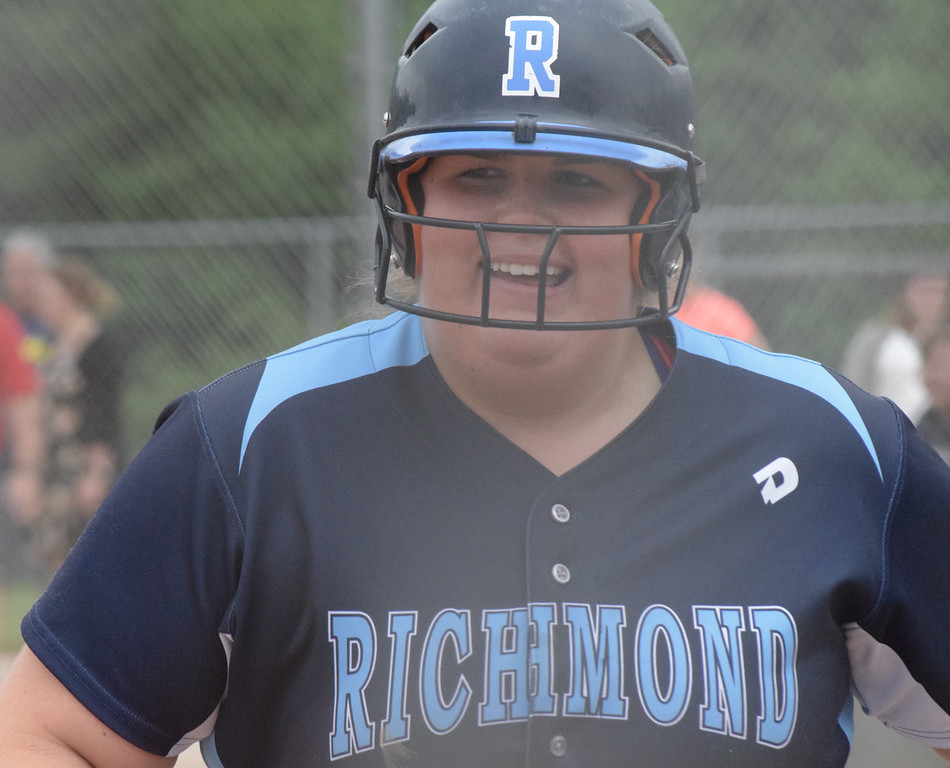 . Autumn Warn smiles on her way to the dugout after scoring Richmond\'s first run against Divine Child.