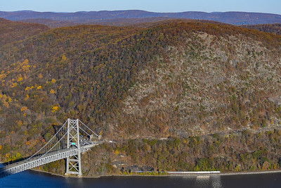 Amtrak Empire Service heads beneath Bear Mountain Bridge in the fall.