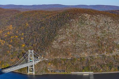 Amtrak Empire Service heads beneath Bear Mountain Bridge in the fall.