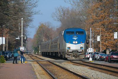 Amtrak's Carolinian rolls through Ashland, VA as a couple wave to the train.