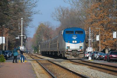 Amtrak's Carolinian rolls through Ashland, VA as a couple wave to the train.