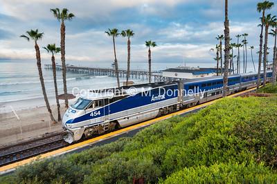 A northbound Pacific Surfliner heads through San Clemente, CA past the pier. SNP