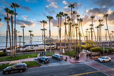 The 168 powers a Pacific Surfliner train past San Clemente Station and Pier during a beautiful sunset.