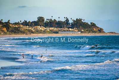 817 leads a Pacific Surfliner train along the shores of San Clemente, CA, with surfers riding waves during last light.
