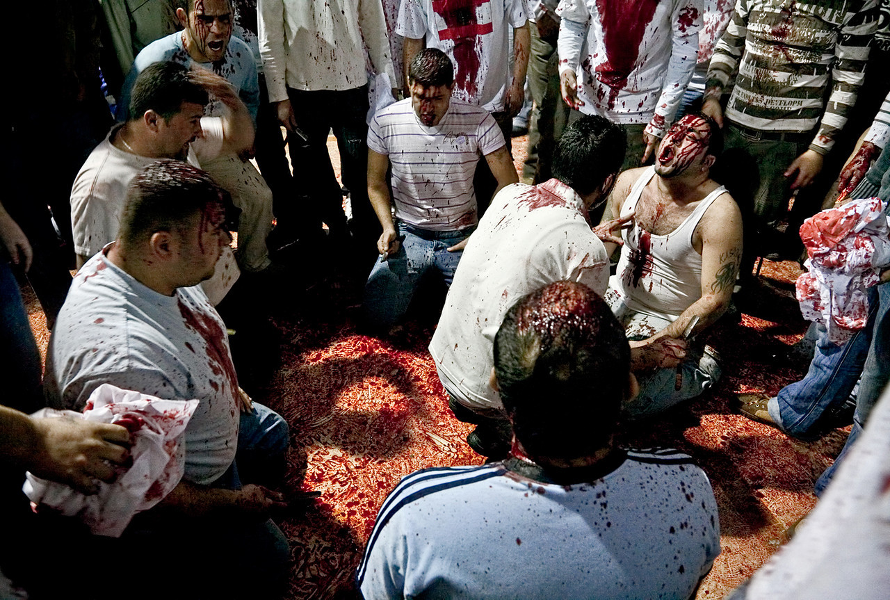 The practice of this type of ma'tam divides Muslim opinion to this day. Although medical personnel were on site to handle any serious injuries, their presence did not dilute the intensity of the event in any way.<br /> <br /> Image: A Red Crescent worker examines a participant of the ma'tam.