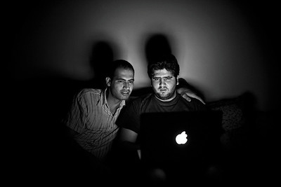 Two Syrian youths work on a Macbook laptop during a power outage.