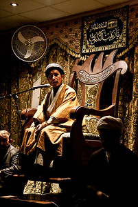 An Afghan Sayyid with black turban sitting on the minbar reading the majlis on the night of the 9th of Moharram.
