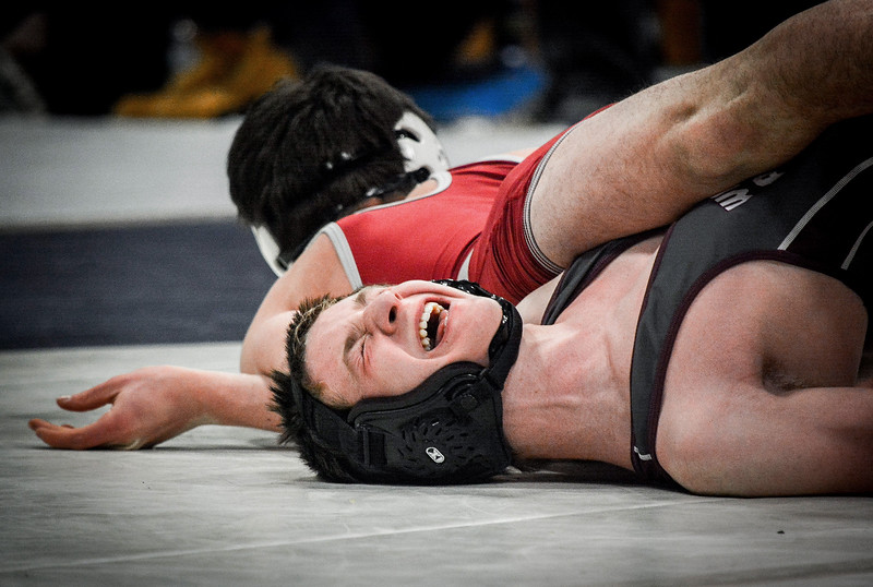 Westford's Conor McDonough trys his hardest to keep both shoulders off the mat as Lowell's Jake Marsh trys to pin him down. SUN/Caley McGuane