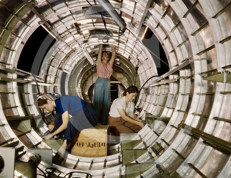 Female workers install fixtures and assemblies to a tail fuselage section of a B-17 bomber at the Douglas Aircraft Company plant, Long Beach, California. Oct 1942