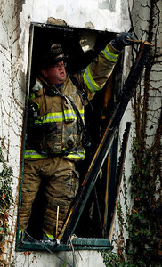 1/3/11 Lake Bluff,IL Highwood firefighter Karl Klotz clears a window frame at the house fire at 117 Woodland in Lake Bluff. | Joel Lerner~Sun-Times Media