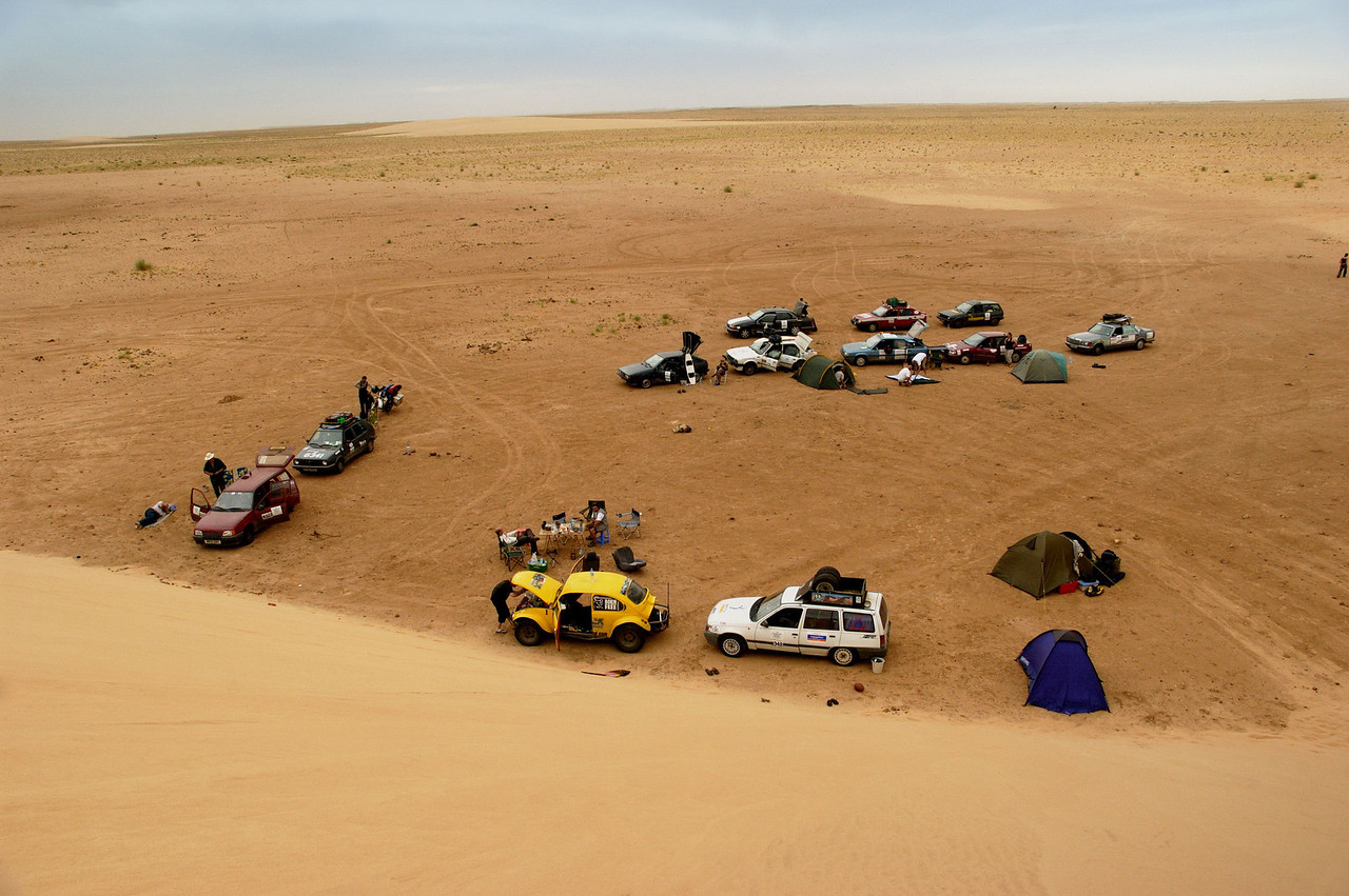 Modernday nomads from the 2006 Plymouth-Banjul Rally set up camp in the lee of a huge dune in the Mauritanian Sahara.