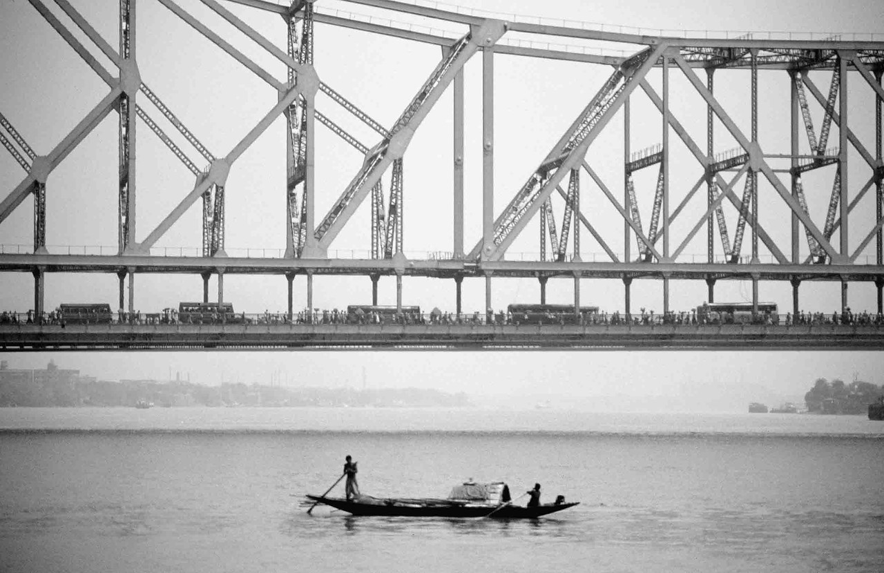 INDIA -Kolkata's Howrah Bridge is the busiest in the world - supporting a daily stream of 100,000 vehicles and well over a million pedestrians