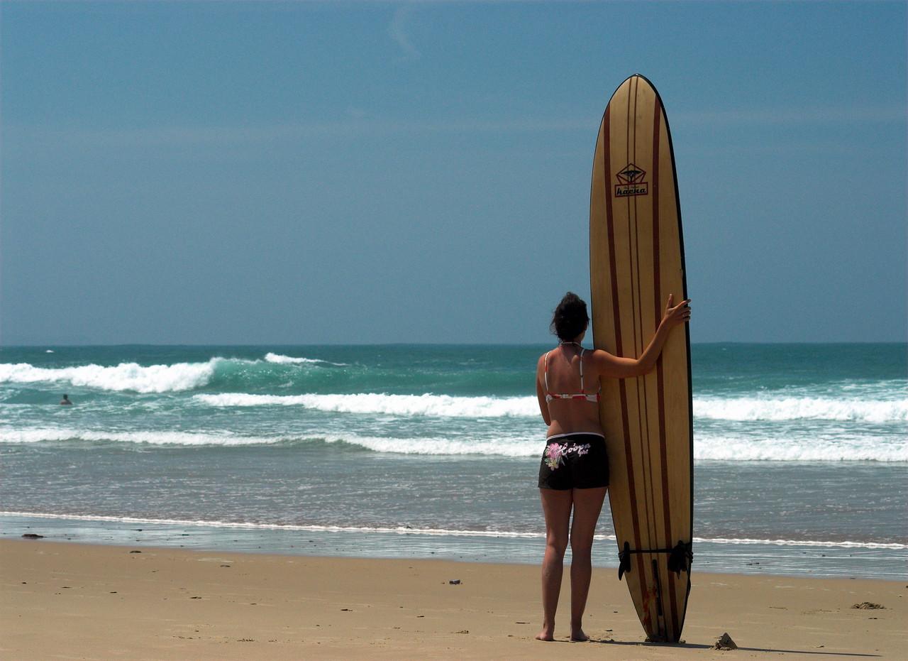 Longboarding beach babe at Praia de Arrifana, Algarve, Portugal