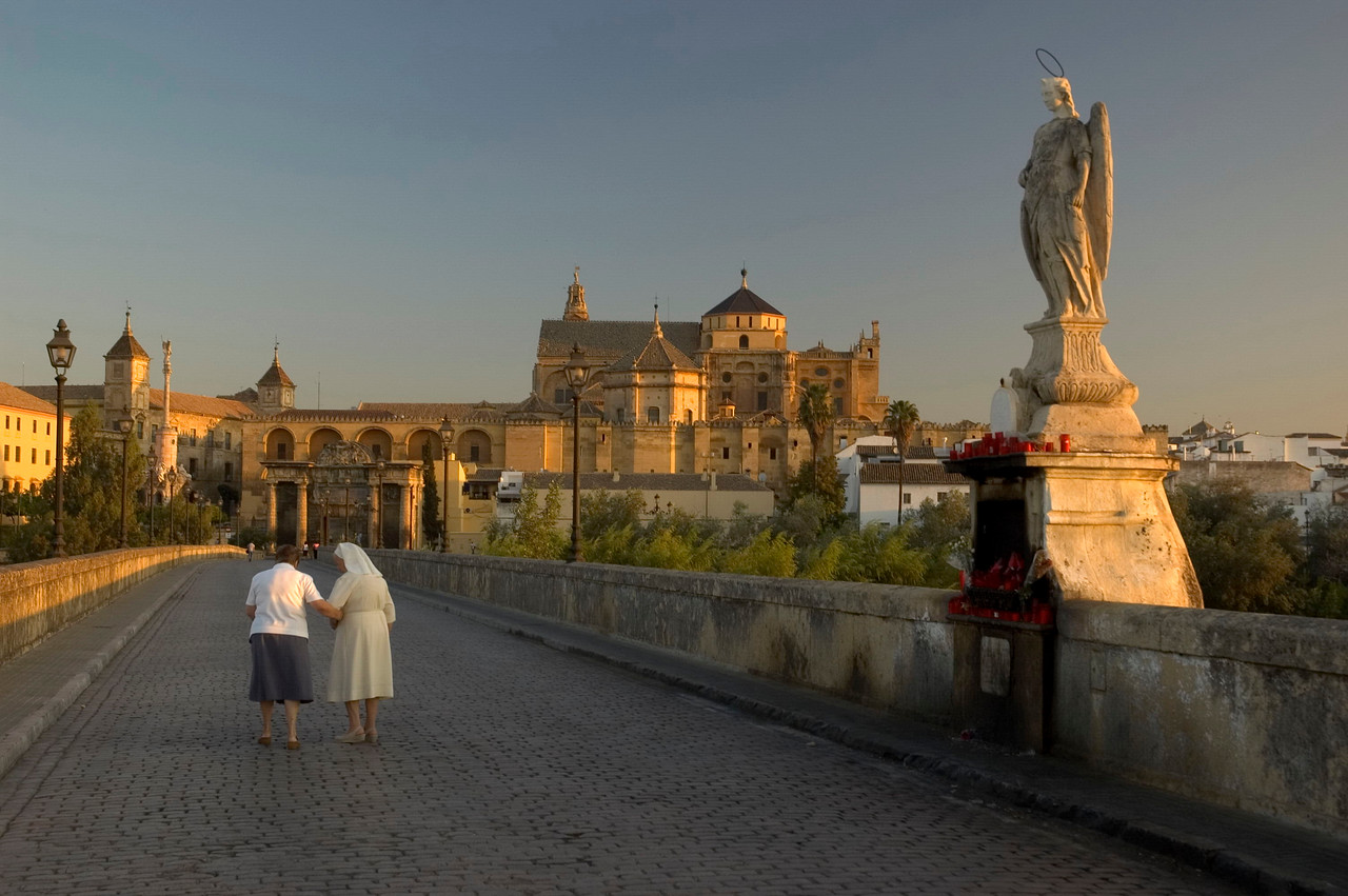 A nun pauses on the Roman bridge, in front of the image of San Rafael - patron saint and protector of Cordoba