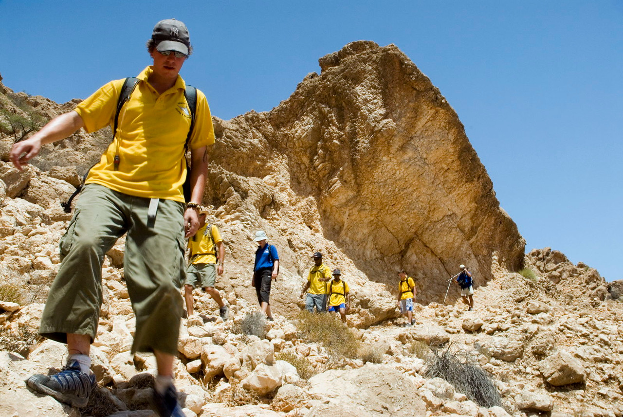 A group of trekkers scramble across a typically desolate landscape in the Eastern Hajars (near Kaftary Cave)